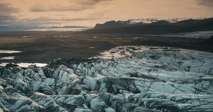 Aerial view of the ice lagoon on sunset. Copter flying over the glacier Vatnajokull with volcanic ash in Iceland. stock video