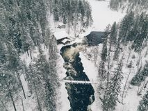 Aerial view of Icy river flowing through a beautiful snowy winter scenery in Oulanka National Park. Finland. Aerial view of Icy river flowing through a Stock Images