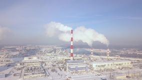 Aerial view industrial city and smoking chimney on winter landscape. Drone view smoke chimney pipe on chemical plant. Industrial factory building and boiler stock video