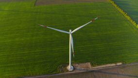 Windmill farm generating green power. View of windmill rotating in rural area.