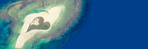Aerial view of an island in the shape of a heart. Elements of this image are furnished by NASA royalty free stock photos