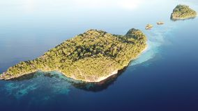 Aerial View of Islands and Coral Reefs in Raja Ampat. A rugged limestone island is surround healthy coral reef in Raja Ampat, Indonesia. This unique, equatorial stock footage