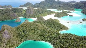 Aerial View of Islands in Wayag, Raja Ampat. Rugged limestone islands, surrounded by coral reefs, are found in an idyllic, tropical lagoon in Wayag, Raja Ampat stock video