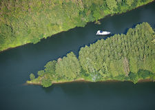 Aerial view : isolated boat on a river. Surrounded by forest Stock Photos
