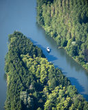 Aerial view : Isolated boat on a river. Surrounded by forest Royalty Free Stock Photos