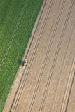 Aerial View : isolated combine harvester working. In the fields forming cultivation lines Royalty Free Stock Photos