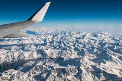 Aerial view of the Italian Swiss Alps in winter, with generic aeroplane wing. Snowcapped mountain range and glaciers. Expansive vi Royalty Free Stock Images