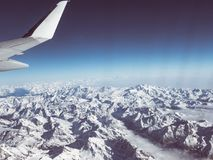 Aerial view of the Italian Swiss Alps in winter, with generic aeroplane wing. Snowcapped mountain range and glaciers. Expansive vi. Ew, clear blue sky Royalty Free Stock Image