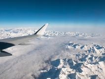 Aerial view of the Italian Swiss Alps in winter, with generic aeroplane wing. Snowcapped mountain range and glaciers. Expansive vi. Ew, clear blue sky Stock Images