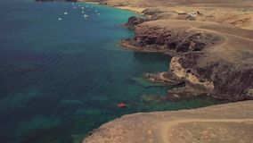Aerial view of the jagged shores and beaches of Lanzarote, Spain, Canary. Red dinghy moored in a cove. Papagayo. Aerial view of the jagged shores and beaches of stock video footage