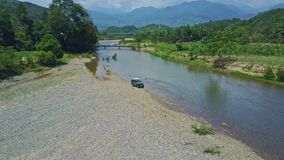 Aerial view jeep drives on gravel river bank against landscape. Nha Trang, Khanh Hoa/Vietnam - April 28 2017: Aerial view military jeep drives on gravel wet stock video footage