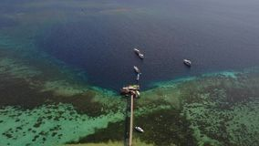 Aerial view of jetty on Kanawa Island. Beautiful aerial view footage of a wooden jetty and boats on the Kanawa Island Resort, an island located near Bali stock video