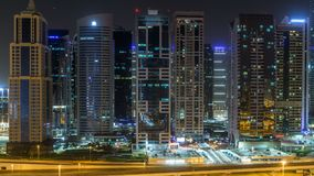 Aerial view of Jumeirah lakes towers skyscrapers during all night timelapse with traffic on sheikh zayed road. Aerial view of Jumeirah lakes towers with stock video footage