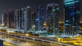 Aerial view of Jumeirah lakes towers skyscrapers during all night timelapse with traffic on sheikh zayed road. Aerial view of Jumeirah lakes towers with stock video