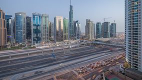 Aerial view of Jumeirah lakes towers skyscrapers day to night timelapse with traffic on sheikh zayed road. Aerial view of Jumeirah lakes towers skyscrapers day stock footage