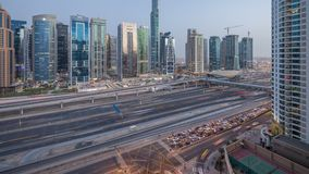Aerial view of Jumeirah lakes towers skyscrapers day to night timelapse with traffic on sheikh zayed road. Aerial view of Jumeirah lakes towers skyscrapers day stock video