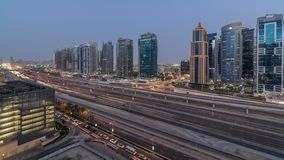 Aerial view of Jumeirah lakes towers skyscrapers day to night timelapse with traffic on sheikh zayed road. Aerial view of Jumeirah lakes towers skyscrapers day stock video footage