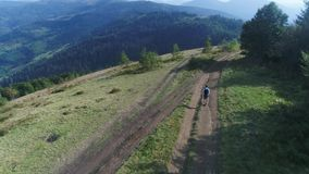 Aerial view. 4k. Man with a backpack walks along the mountain road in a sunny day. Vocation stock video footage
