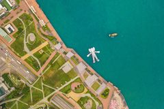 Aerial view of KAWS companion, giant sculpture floating on water. Figure in Victoria Harbour, Hong Kong. Republic of China.  stock photo
