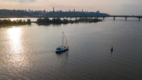 Aerial view of Kiev city skyline on sunset, yacht sailing in Dnieper river from above, Kyiv. Ukraine Stock Image