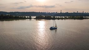 Aerial view of Kiev city skyline on sunset, yacht sailing in Dnieper river from above, Kyiv. Ukraine Stock Photos