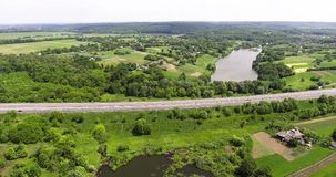 Aerial view of the Kiev-Odessa highway. Flying over cars, trucks, near a green field, a quiet river and a beautiful. Green forest stock video footage