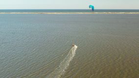 Aerial view of kitesurfer gliding and jumping across ocean stock footage