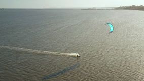 Aerial view of kitesurfer gliding and jumping across ocean stock video footage