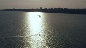 Aerial view of kitesurfer gliding and jumping across ocean stock video