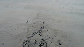 Aerial view of Lady walking on the the famous Magheraroarty beach - Machaire Rabhartaigh - on the Wild Atlantic Way in stock video footage