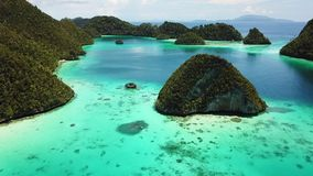 Aerial View of Lagoon and Islands in Raja Ampat. Rugged limestone islands, surrounded by coral reefs, are found in an idyllic, tropical lagoon in Wayag, Raja stock video footage