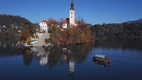 Aerial view of Lake Bled, Slovenia. Flight over of Bled Island Blejski otok with pilgrimage church of the Assumption of Mary and Bled castle on Lake Bled over stock footage