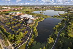 Aerial View of Lake and Community Center. Aerial view of a lake beside a community center and grade school with walking paths and bridge at The Glen in Glenview Stock Photos