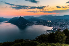 Aerial view of the lake Lugano surrounded by mountains and evening city Lugano on during dramatic sunset, Switzerland, Alps. Stock Photos