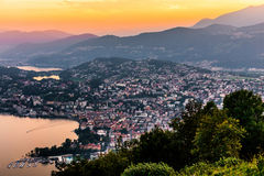 Aerial view of the lake Lugano surrounded by mountains and evening city Lugano on during dramatic sunset, Switzerland, Alps. Stock Images