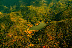 Aerial View of Lake Surrounded by Beautiful Mountain Range. Aerial view of small lake surrounded by beautiful mountain range with warm sunlight during flight Stock Photo
