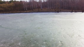 Aerial view of a landscape of a frozen lake on a sunny early spring day stock footage