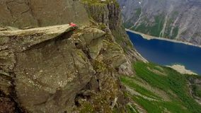 Aerial view of the landscape of Norway. Guy sits on the edge of a huge rock against the backdrop of a wonderful mountain. Aerial view of the enchanting landscape stock video