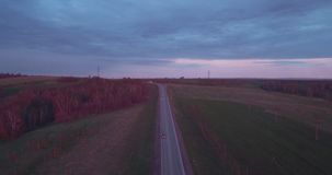 Aerial view of landscape with a ride on the highway trucks and a few cars at sunset and clouds. 4K. Aerial view of landscape with a ride on the highway trucks stock footage
