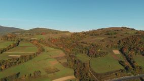 Autumn in the Carpathian Mountains. Ukraine. Aerial View Of The Landscape With Small Village In Mountains, Highway Through the Village in the Carpathian stock footage