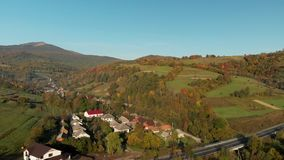 Aerial View of a Village in the Carpathian Mountains. Ukraine. Aerial View Of The Landscape With Small Village In Mountains, Highway Through the Village in the stock video
