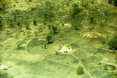 Aerial view of landscape in South Sudan. Some small huts at a dirt road crossing Royalty Free Stock Images