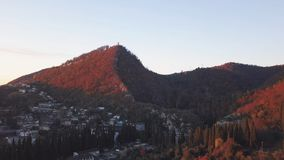 Aerial view - landscape of tree, mountain from the top of mountain in sunset time. Clip. Top view of the mountain city. At sunset Royalty Free Stock Photos