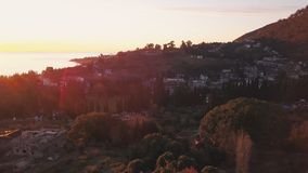 Aerial view - landscape of tree, mountain from the top of mountain in sunset time. Clip. Top view of the mountain city. At sunset Royalty Free Stock Photography