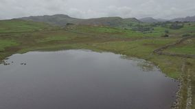 Langdale Pikes and Blea Tarn in Lake District, UK from the air. Aerial view on the Langdale Pikes and Blea Tarn in the English Lake District in autumn stock video footage