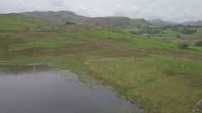 Langdale Pikes and Blea Tarn in Lake District, UK from the air. Aerial view on the Langdale Pikes and Blea Tarn in the English Lake District in autumn stock footage