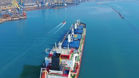 Aerial view. Large cargo ship enters the port city with port cranes. Aerial view. Large cargo ship enters the port city with port cranes stock video footage