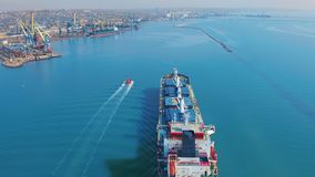 Aerial view. Large cargo ship enters the port city with port cranes. Aerial view. Large cargo ship enters the port city with port cranes stock video