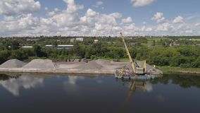 River crane excavator on barge. Aerial view large crane an excavator mounted on barge. Excavator on river for unloading and loading sand and rubble stock video