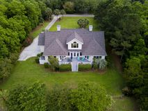 Aerial view of large home with on wooded grassy property stock photos